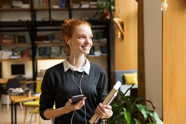 Rudowłosy student pozuje w pomieszczeniu w bibliotece, trzymając książki, słuchając muzyki przez słuchawki i używając telefonu komórkowego