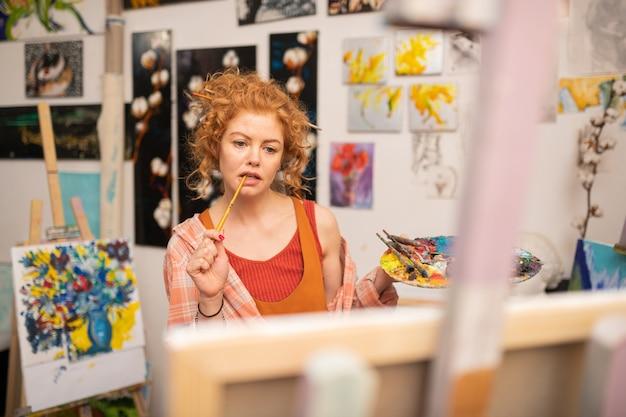 Rudowłosy student sztuki. rudowłosy student sztuki czuje się zaangażowany w wykonywanie zadań domowych na uniwersytecie