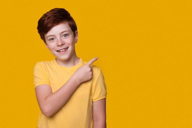 Rudy chłopiec coś reklamuje