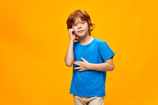Rudy chłopiec trzymający rękę w pobliżu twarzy dzieciństwo niebieski t-shirt żółty