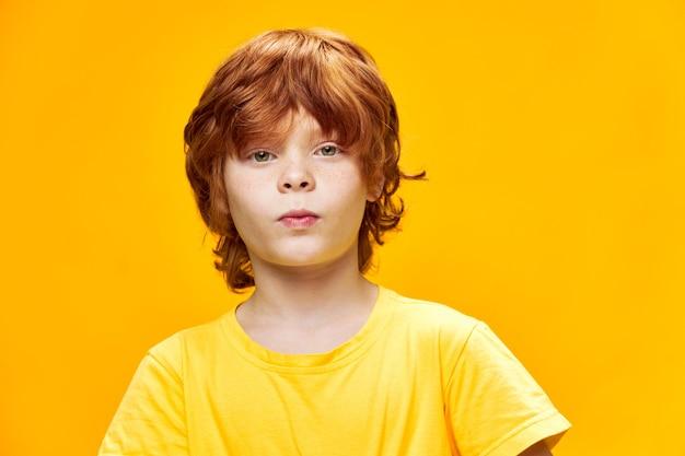 Rudy chłopiec ubrany w żółtą koszulkę przycięty widok patrząc w przyszłość z dzieciństwa
