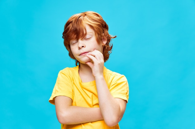 Rudy chłopiec z zamkniętymi oczami trzyma rękę na twarzy przycięty widok