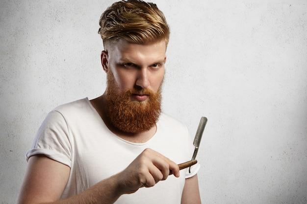 Rudy fryzjer lub fryzjer z puszystą brodą, ubrany w białą koszulkę, demonstrujący ostre ostrze brzytwy z prostymi krawędziami w zakładzie fryzjerskim, gotowy do golenia swoich klientów.