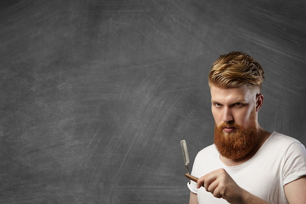 Rudy fryzjer ze stylową fryzurą i brodą hipster, trzymający swój dodatek fryzjerski - staromodną prostą brzytwę.