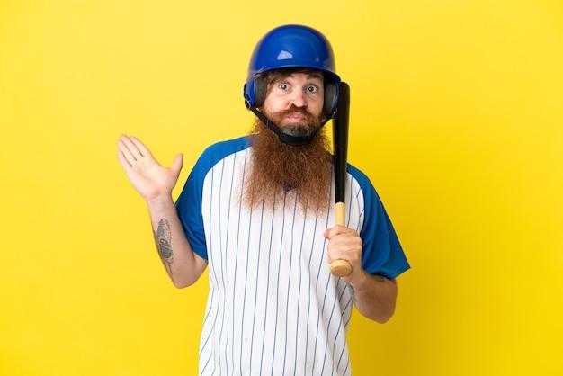 Rudy gracz baseballa z kaskiem i kijem na białym tle na żółtym tle, mający wątpliwości podczas podnoszenia rąk