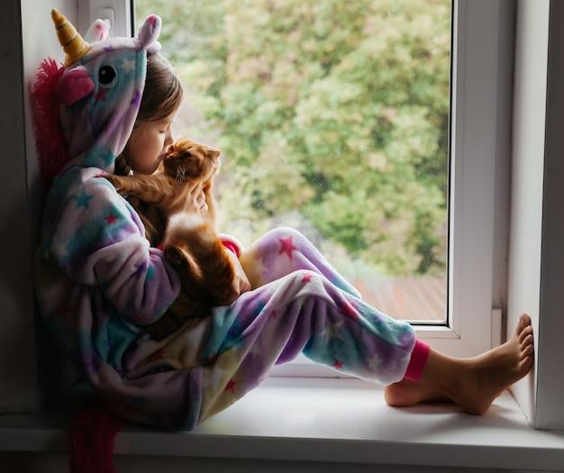 Rudy kotek i mała dziewczynka siedzą na parapecie i wyglądają przez okno.