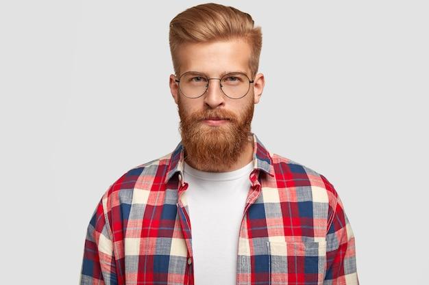 Rudy mężczyzna hipster w okularach i koszuli w kratkę, wygląda poważnie z pewnym siebie wyrazem twarzy, otrzymuje niezbędne informacje