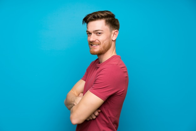 Rudy mężczyzna na izolowanych niebieską ścianą śmiechu