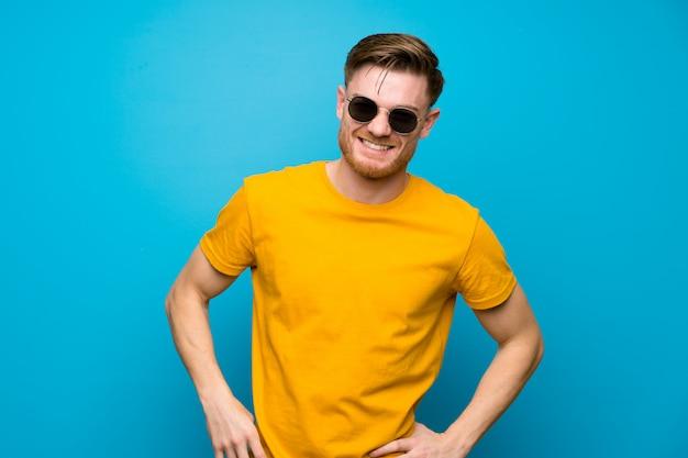 Rudy mężczyzna na niebieską ścianą w okularach i uśmiechnięty
