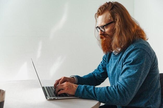 Rudy mężczyzna pracuje na laptopie przy stole
