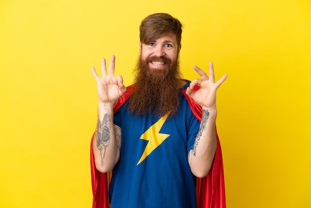 Rudy mężczyzna superbohater na białym tle na żółtym tle pokazując znak ok palcami