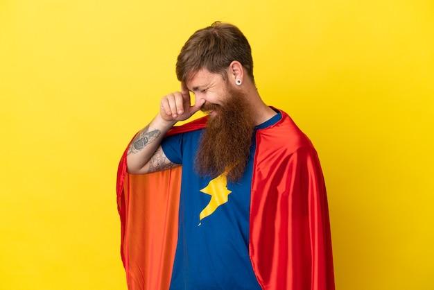 Rudy mężczyzna superbohater na żółtym tle śmiejąc się