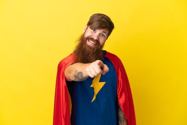 Rudy mężczyzna superbohatera na żółtym tle wskazuje palcem na ciebie z pewną miną