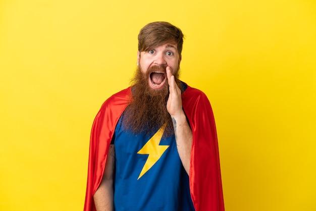 Rudy mężczyzna superbohatera na żółtym tle z zaskoczeniem i zszokowanym wyrazem twarzy