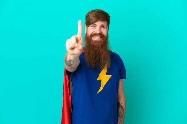 Rudy mężczyzna w kostiumie superbohatera i wskazujący do przodu