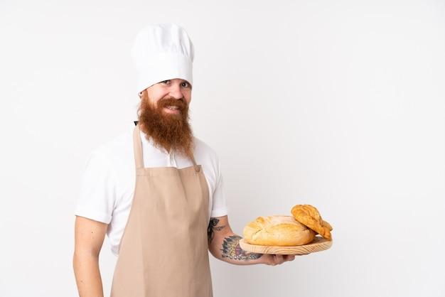 Rudy mężczyzna w mundurze szefa kuchni. męski piekarz trzyma stół z kilka chlebami ono uśmiecha się dużo