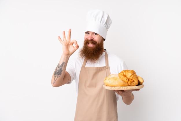 Rudy mężczyzna w mundurze szefa kuchni. męski piekarz trzyma stół z kilka chlebami pokazuje ok znaka z palcami