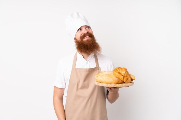 Rudy mężczyzna w mundurze szefa kuchni. męski piekarz trzyma stół z kilka chlebami przyglądającymi up podczas gdy ono uśmiecha się