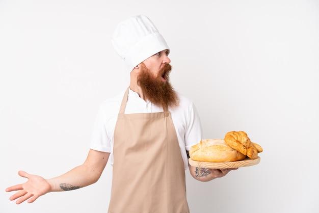 Rudy mężczyzna w mundurze szefa kuchni. męski piekarz trzyma stół z kilka chlebami z niespodzianka wyrazem twarzy