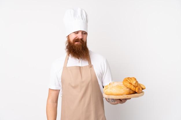 Rudy mężczyzna w mundurze szefa kuchni. męski piekarz trzyma stół z kilka chlebami z smutnym wyrażeniem