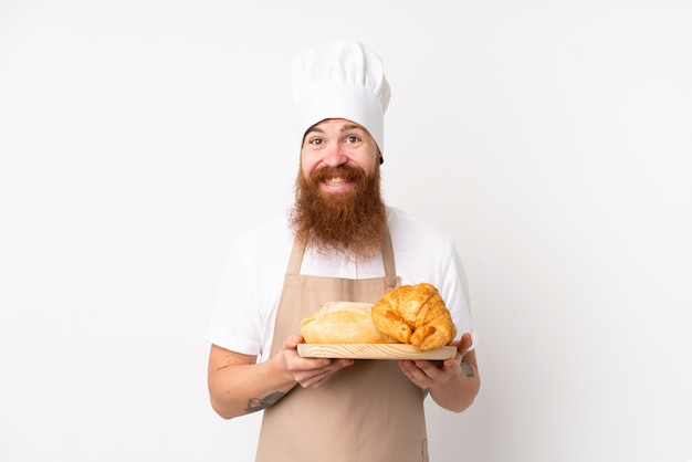 Rudy mężczyzna w mundurze szefa kuchni. męski piekarz trzyma stół z kilka chlebami