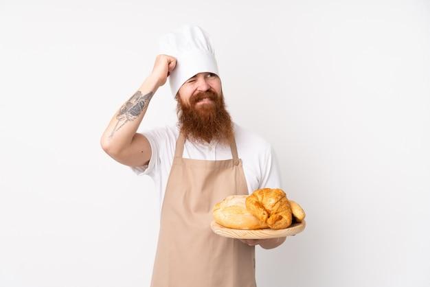 Rudy mężczyzna w mundurze szefa kuchni. męski piekarz trzyma stół z kilkoma chlebami mającymi wątpliwości i mylący wyraz twarzy