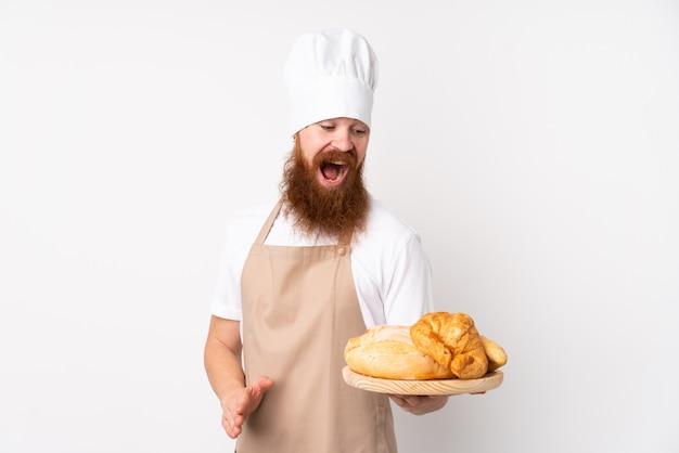 Rudy mężczyzna w mundurze szefa kuchni. męski piekarz trzyma stół z kilkoma chlebami ze zdziwieniem i zszokowanym wyrazem twarzy
