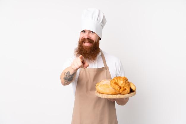 Rudy mężczyzna w mundurze szefa kuchni. mężczyzna piekarz trzyma stół z kilkoma punktami chleba palcem na ciebie z pewnym siebie wyrazem twarzy