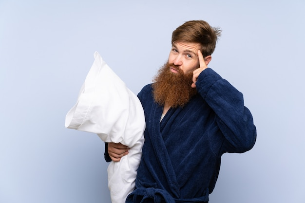 Rudy mężczyzna w piżamie, mając wątpliwości i zmieszany wyraz twarzy