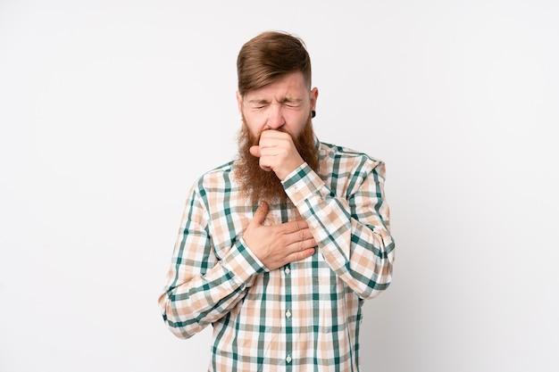 Rudy mężczyzna z długą brodą na białej ścianie na białym tle cierpi na kaszel i źle się czuje