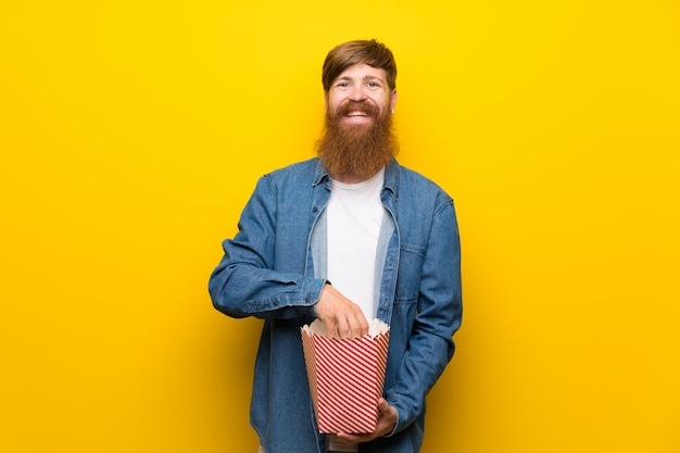 Rudy mężczyzna z długą brodą na pojedyncze żółte ściany, trzymając miskę popcorns