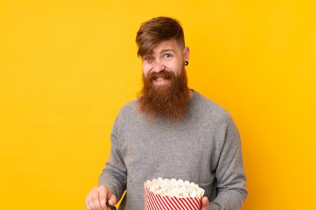 Rudy mężczyzna z długą brodą na żółtej ścianie w okularach 3d i posiadający duże wiadro popcorns