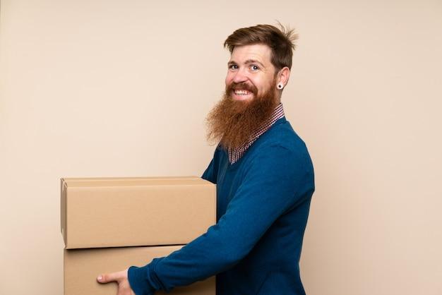 Rudy mężczyzna z długą brodą trzyma pudełko, aby przenieść je na inne miejsce