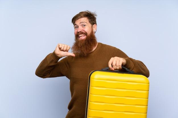 Rudy mężczyzna z długą brodą trzyma walizkę dumny i zadowolony z siebie