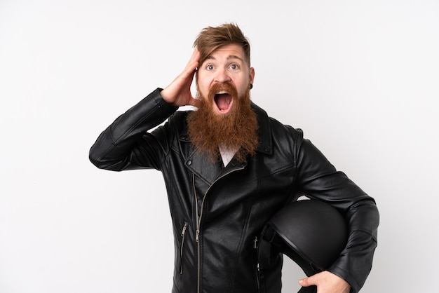 Rudy mężczyzna z długą brodą, trzymając kask motocyklowy na pojedyncze białe ściany zaskoczony i wskazując palcem na bok