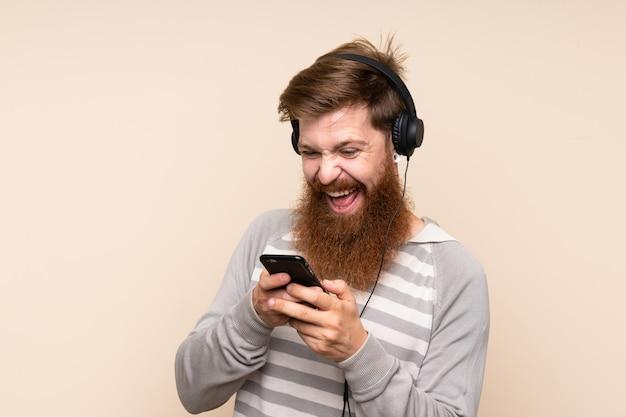 Rudy mężczyzna z długą brodą za pomocą telefonu komórkowego ze słuchawkami i śpiewu