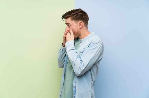 Rudy mężczyzna zakrywa usta i patrzy w bok