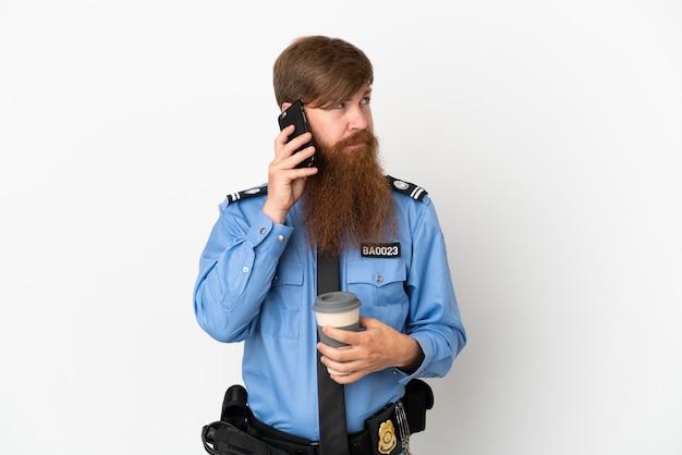 Rudy policjant na białym tle trzymający kawę na wynos i telefon komórkowy