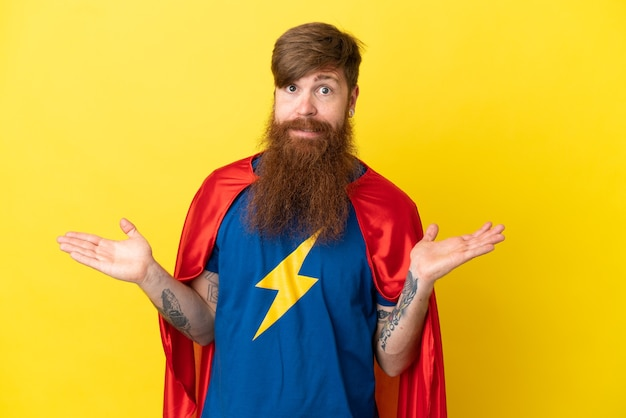 Rudy super hero mężczyzna na białym tle na żółtym tle mający wątpliwości podczas podnoszenia rąk