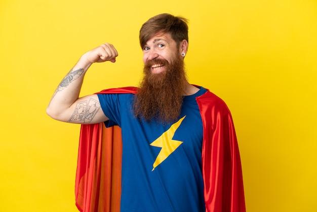 Rudy super hero mężczyzna na żółtym tle robi silny gest
