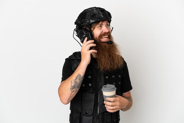 Rudy swat na białym tle trzymający kawę na wynos i telefon komórkowy