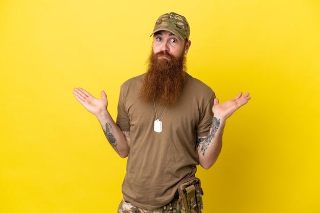 Rudy wojskowy z nieśmiertelnikiem na białym tle na żółtym tle mający wątpliwości podczas podnoszenia rąk
