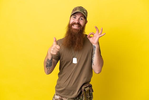 Rudy wojskowy z nieśmiertelnikiem na białym tle na żółtym tle pokazując znak ok i gest kciuka w górę