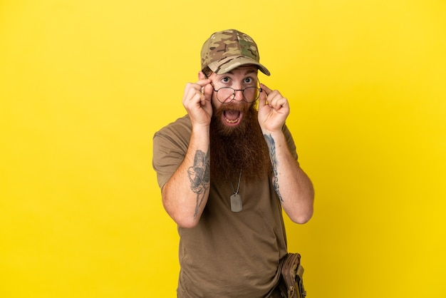Rudy wojskowy z nieśmiertelnikiem na białym tle na żółtym tle w okularach i zaskoczony