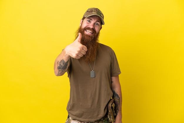 Rudy wojskowy z nieśmiertelnikiem na białym tle na żółtym tle z kciukami do góry, ponieważ stało się coś dobrego