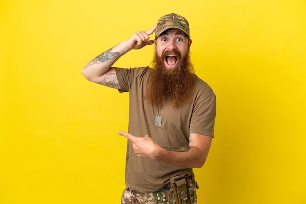 Rudy wojskowy z nieśmiertelnikiem na żółtym tle zaskoczony i wskazujący palcem w bok