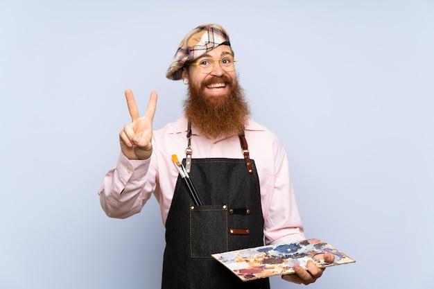 Rudzielec artysty mężczyzna z długą brodą trzyma paletę nad odosobnioną błękit ścianą uśmiecha się znak zwycięstwa i pokazuje