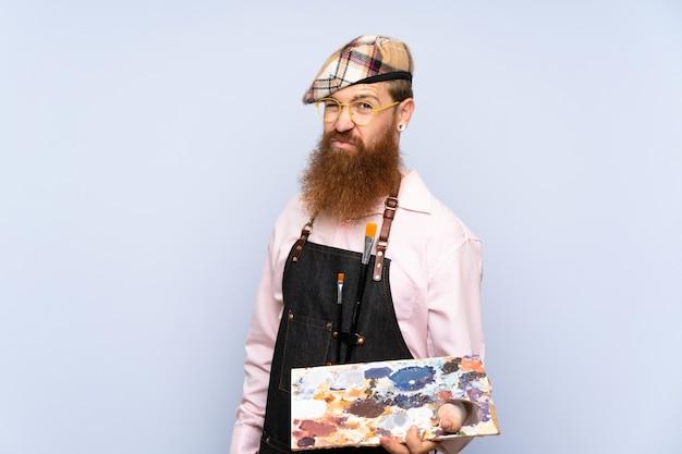 Rudzielec artysty mężczyzna z długą brodą trzyma paletę nad odosobnioną błękit ścianą z smutnym wyrażeniem