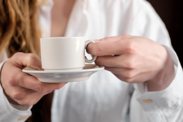 Rudzielec biała dziewczyna pije kawę w białej koszula, zamyka up