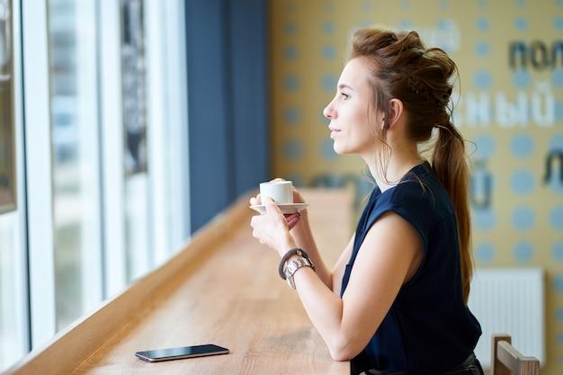 Rudzielec biała dziewczyna w granatowej bluzce pije kawę w kawiarni i ogląda przy oknie